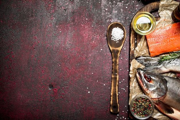 Frischer fisch mit einem stück filet und gewürzen auf rustikalem tisch.