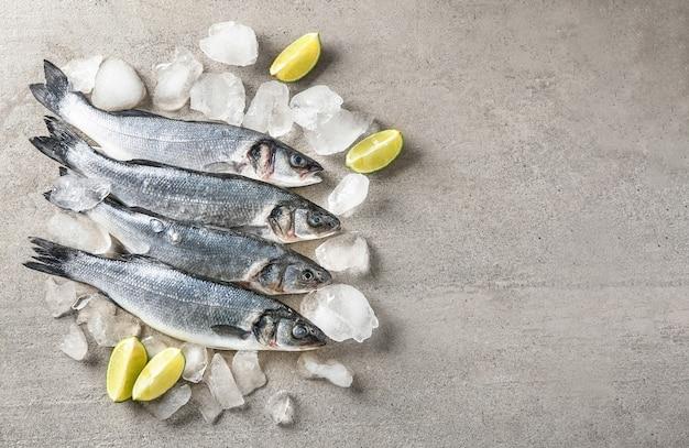 Frischer fisch mit eis auf grauem tisch
