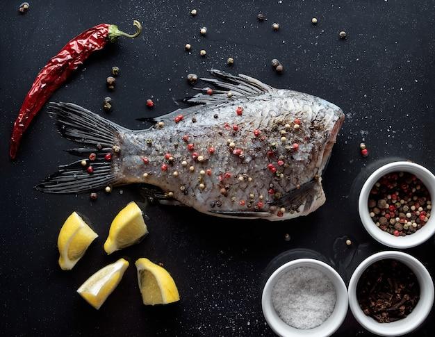 Frischer fisch mit pfeffer und gewürzen zum backen bestreut.