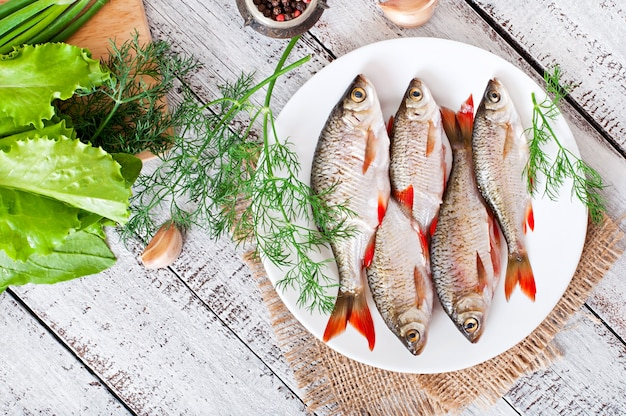 Frischer fisch mit rosmarin in einer platte auf holztisch