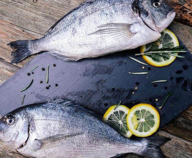 Frischer fisch mit zitrone auf rustikalem brett