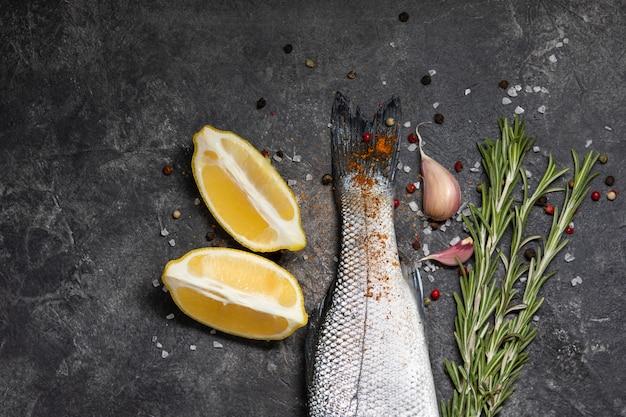 Frischer fisch seebarsch und zutaten zum kochen, zitrone und rosmarin. dunkler hintergrund draufsicht.