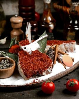Frischer fisch unter rotem pfeffer auf dem tisch