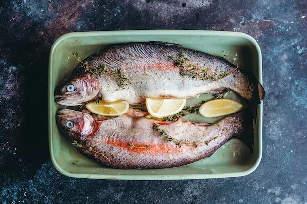 Frischer fisch vor dem kochen, gewürzt mit kräutern, pfeffer, thymian und zitrone.