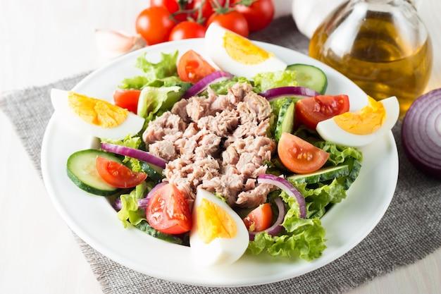 Frischer fischthunfischsalat aus tomaten, ruccola, thunfisch, eiern, rucola, crackern und gewürzen.