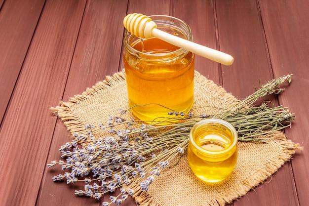Frischer flüssiger honig in den glasgefäßen mit einem hölzernen honigschöpflöffel