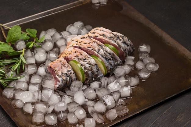 Frischer flussfisch auf metallschale mit schmelzendem eis. zitrone und rosmarinzweige.