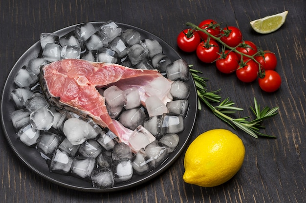 Frischer flussfisch auf schmelzendem eis auf schwarzer keramikplatte. zitrone und zweig kirschtomate und rosmarin.