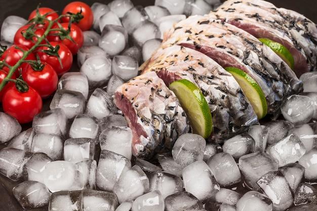 Frischer flussfisch auf schmelzendem eis. zitrone und zweig kirschtomate.