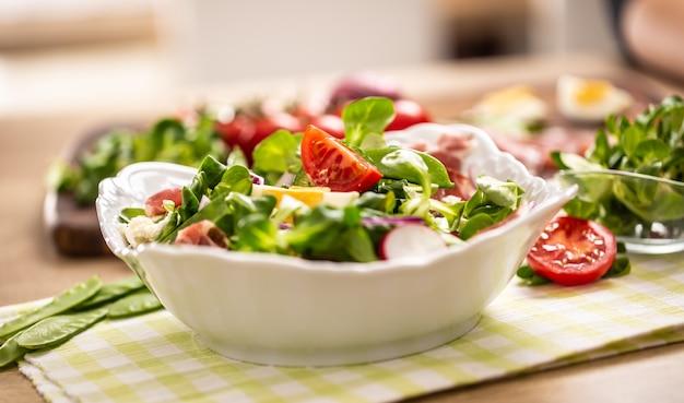 Frischer frühlingssalat mit grünen blättern tomaten eierrettich rote zwiebeln junge erbsen prosciutto feta-käse und olivenöl.