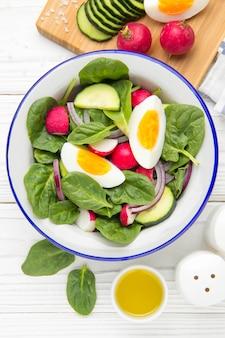 Frischer frühlingssalat mit spinat, rettich, gurke und ei.