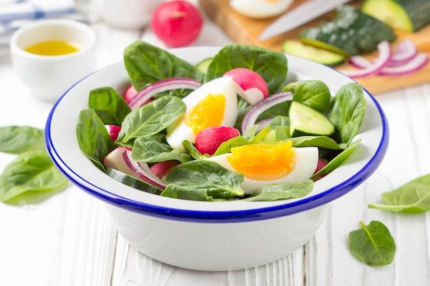 Frischer frühlingssalat mit spinat, rettich, gurke und ei