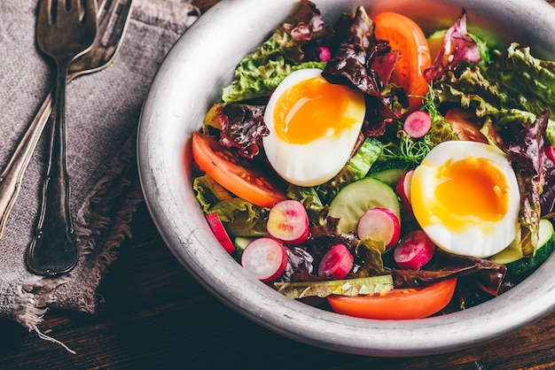 Frischer frühlingssalat mit tomate, rettich, gurke, rotem blattsalat und gekochten eiern in metallschüssel