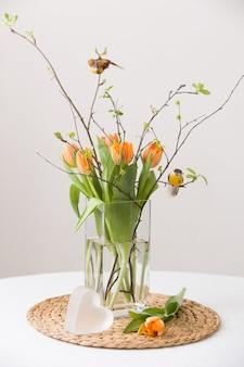 Frischer frühlingsstrauß aus orangefarbenen tulpen und grünen blättern und kleinen vögeln in einer schönen kristallglasvase