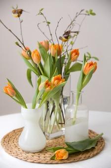 Frischer frühlingsstrauß aus orangefarbenen tulpen und grünen blättern und kleinen vögeln in schönen kristallglasvasen