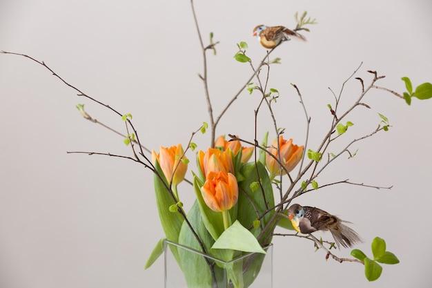 Frischer frühlingsstrauß aus orangefarbenen tulpen und grünen blättern und zwei kleine vögel in schöner kristallglasvase