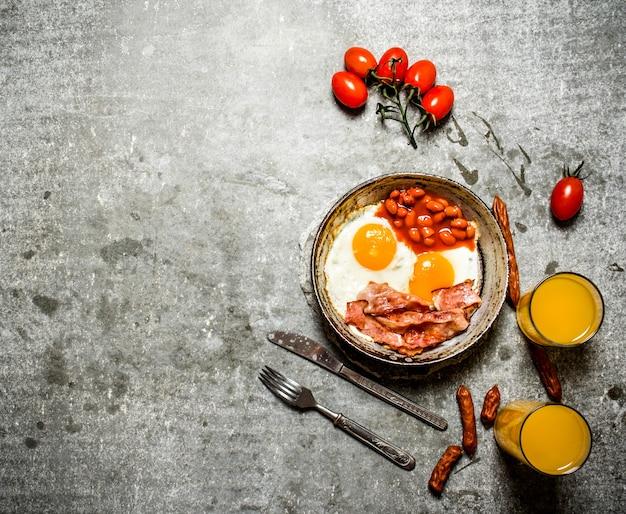 Frischer frühstücksspeck mit spiegeleiern und bohnen orangensaft und tomaten auf dem steintisch