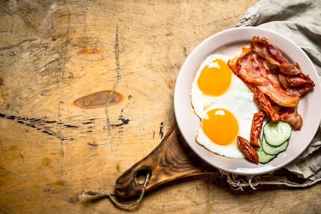 Frischer frühstücksteller spiegeleier mit speck und tomaten auf einem holztisch