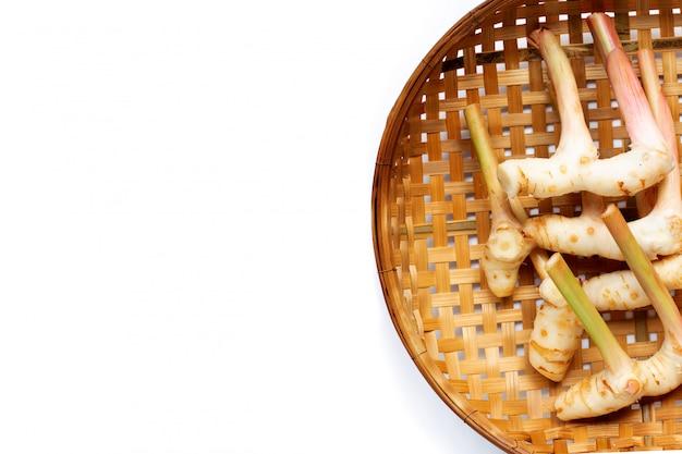 Frischer galangal auf hölzernem bambusdreschkorbhintergrund.