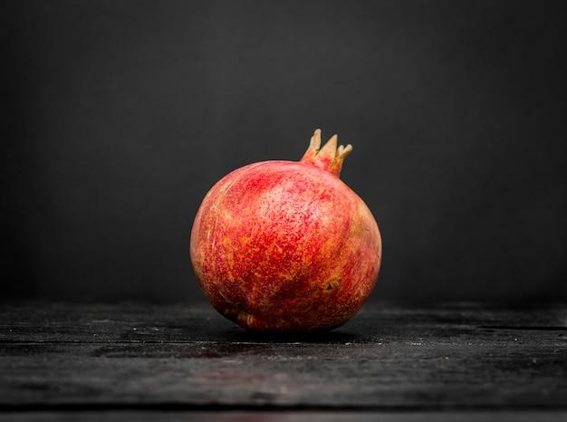 Frischer ganzer granatapfel auf einem schwarzen holz schließen