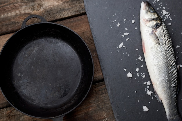 Frischer ganzer wolfsbarschfisch auf einer tafel, daneben eine leere runde schwarze pfanne