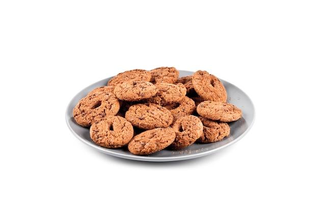 Frischer gebackener schokoladensplitterplätzchenhaufen auf der grauen platte lokalisiert auf weiß