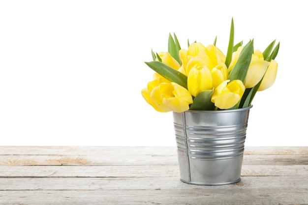 Frischer gelber tulpenblumenstrauß über holztisch. isoliert auf weißem hintergrund