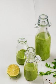 Frischer gemachter gesunder grüner smoothie diente in den flaschen auf weißem hintergrund.