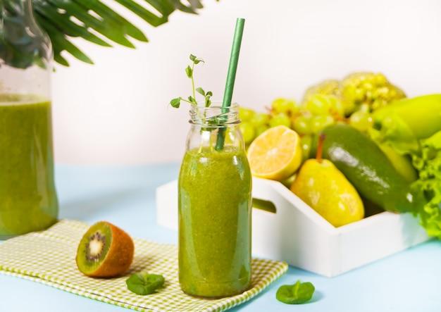 Frischer gemischter grüner smoothie in einer kleinen glasflasche mit obst und gemüse auf der oberfläche. gesundheits- und entgiftungskonzept.