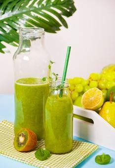 Frischer gemischter grüner smoothie in glasflaschen mit obst und gemüse. gesundheits- und entgiftungskonzept.