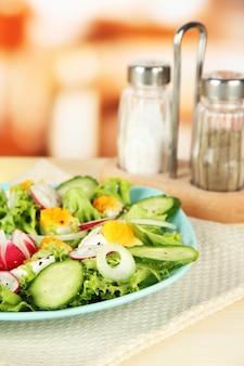 Frischer gemischter salat mit eiern, salatblättern und anderem gemüse auf farbtafel, auf hellem hintergrund