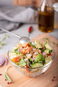 Frischer gemüse- und quinoasalat in einer glasschüssel auf dem tisch, nahaufnahme