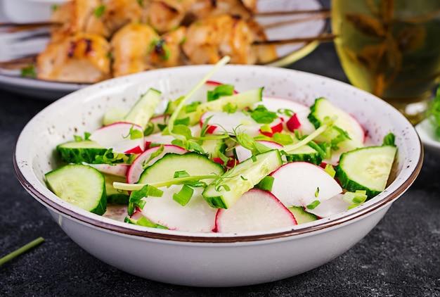 Frischer gemüserettich-gurken-salat mit frühlingszwiebeln und microgreen-erbsen