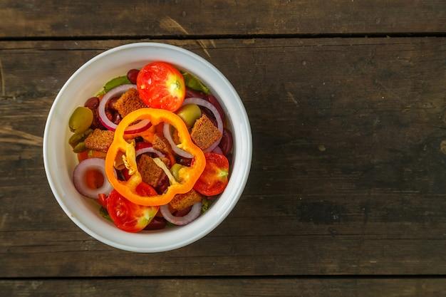Frischer gemüsesalat in einer salatschüssel auf einem holztisch. horizontales foto
