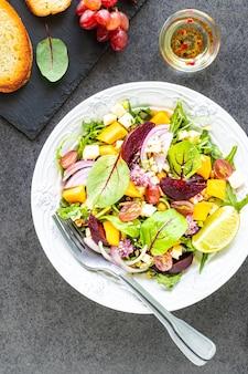 Frischer gemüsesalat mit rüben, rucola, roten zwiebeln und sauerampfer in einem weißen teller mit kürbis und trauben