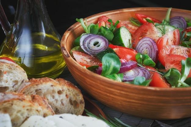 Frischer gemüsesalat mit tomaten, gurken und zwiebeln. serviert mit käse, gemüse, olivenöl und brot