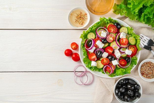 Frischer gemüsesalat und bestandteile auf einem weißen hölzernen hintergrund. das konzept der richtigen ernährung.