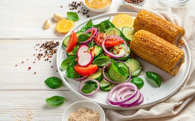 Frischer gemüsesalat und gerösteter mais auf heller wand mit gewürzen basilikum und zitrone