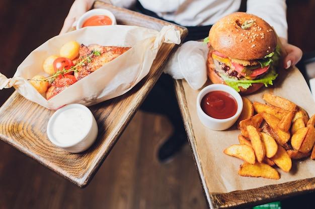 Frischer geschmackvoller burger und pommes-frites auf holztisch.