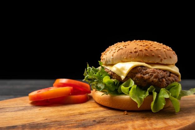 Frischer geschmackvoller selbst gemachter hamburger mit frischgemüse auf einem schneidebrett.