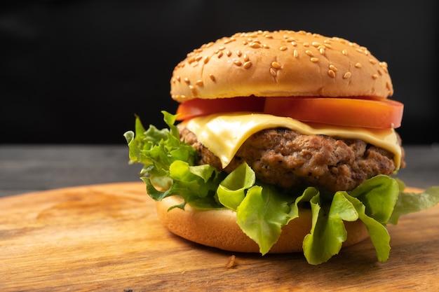 Frischer geschmackvoller selbst gemachter hamburger mit frischgemüse und käse auf einem schneidebrett.