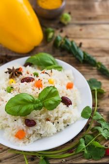 Frischer geschmackvoller vegetarischer reis auf platte mit basilikumblättern und -petersilie