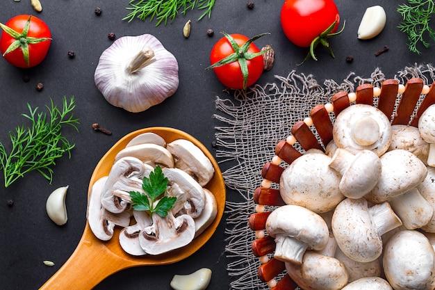 Frischer geschnittener champignon im hölzernen löffel auf einer schwarzen brandung. kochen von hausgemachten gerichten aus weißem, reifem pilz mit petersilie, dill und gemüse.