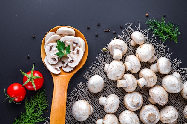 Frischer geschnittener champignon im hölzernen löffel und in der gruppe weißen reifen pilzen auf einer schwarzen brandung für das kochen von selbst gemachten tellern.