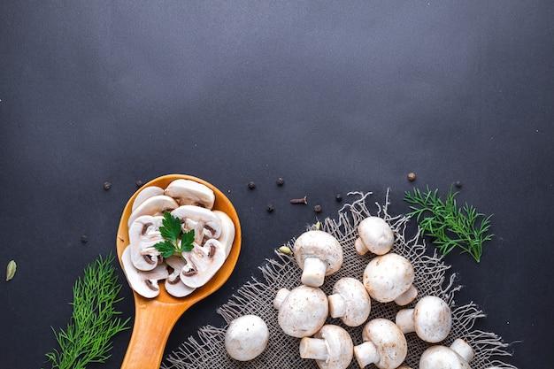 Frischer geschnittener champignon mit petersilie im hölzernen löffel und im dill, weiße reife pilze auf einer schwarzen brandung für das kochen von selbst gemachten köstlichen tellern. kopieren sie platz