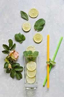 Frischer geschnittener kalk mit grünen tadellosen blättern und glas auf grauem tabellenhintergrund. ansicht von oben