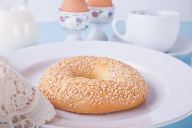 Frischer gesunder bagel auf einer weißen platte mit tasse kaffee
