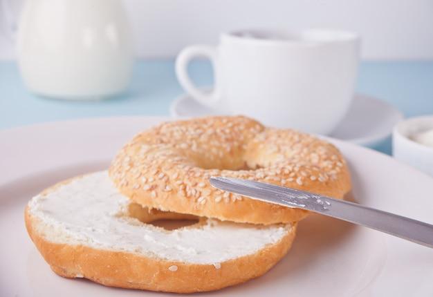 Frischer gesunder bagel auf einer weißen serviette mit tasse kaffee, frischkäse und eiern zum frühstück.
