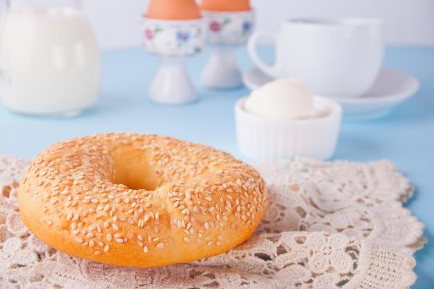 Frischer gesunder bagel auf einer weißen serviette mit tasse kaffee