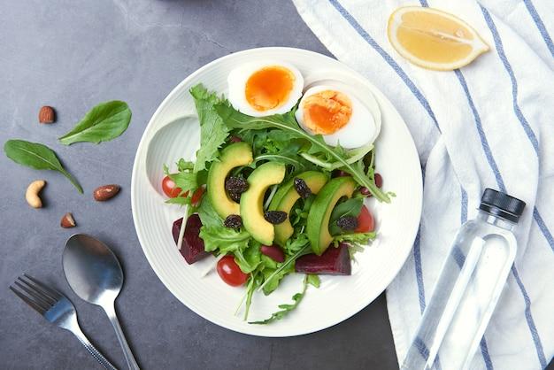 Frischer gesunder gemüsesalat mit ei, tomate, avocado, spinat, kopfsalat in der platte auf tabelle.